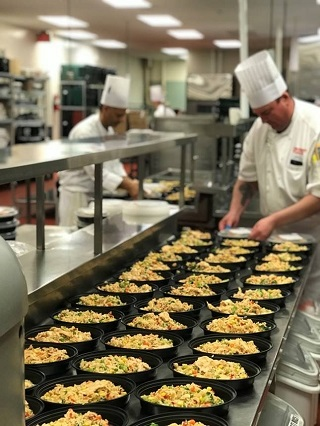 The image shows 3 rows of portioned meals being prepared in a commercial kitchen by a chef. On the left side of the photograph further back from the first chef appears a second chef also preparing portioned meals.