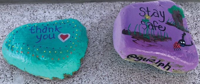 "The image shows two painted the rocks. The rock on the left is turquoise and has the words ""thank you"" painted on with a heart. The rock on the right is painted purple and has a nature scene on top, with the words ""stay safe"" and ""@guelph"" painted in black."