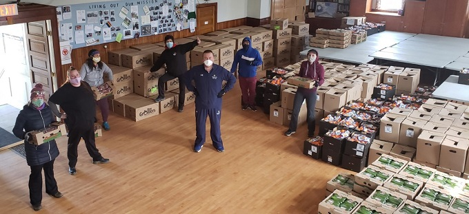 The image shows volunteers wearing masks and gloves - observing social distancing - while packing and carrying boxes of fresh produce for distribution to families in need.