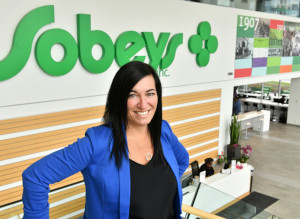 This is a picture of Sheri Evans standing in front of a Sobeys sign. Sheri is the Local Development Manager, Ontario Field Merchandising for Sobeys Ontario who is responsible for making it possible for smaller-to-medium sized vendors to supply stores on a regional basis.