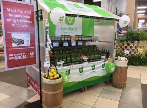This is a picture of a retail display at a Sobeys store located in Ajax. The retail display is prominently featuring Ontario asparagus accompanied by Foodland Ontario point-of-sale materials, such as a flag, balloons and base wrap, and signage from Sobeys communicating to eat better and choose local. The retail display is a promotional tactic used by the Foodland Ontario program in conjunction with Ontario farmers and retail grocery stores, such as Sobeys, to encourage more shoppers to buy local.