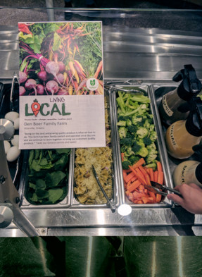 This is a picture of a communication tool placed at St Paul's University College's Wheelock Dining Hall at the University of Waterloo above a salad bar. The communication tool shown is signage about Chartwells Buy Local Program featuring a cornucopia of Ontario vegetables and identifying a local family farm supplying St. Paul's University College. Chartwells is making communication tools co-branded with the Foodland Ontario logo available to colleges, universities and schools to promote local food on their campuses.