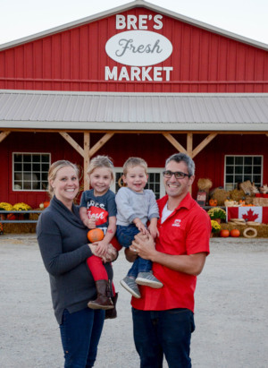 This is a picture of Breann and Kyle Gillespie with their two children standing in front of their store at their on-farm market. Breann and Kyle are the owners of Bre's Fresh Market located near Tillsonburg in Oxford County.