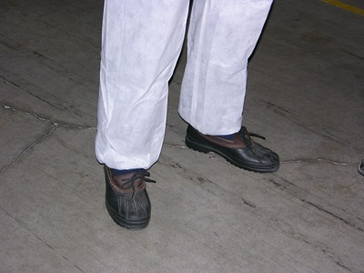Figure 6. Photo of a visitor to the greenhouse dressed in coveralls and disinfected boots.