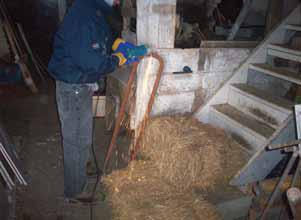 Picture of a man, inside a barn, using a grinder on a piece of metal.  The person is grinding over two bales of hay which are combustible materials.  This activity should be done outside the barn and away from anything that might catch fire.