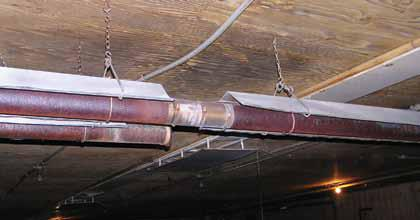 Picture of a radiant tube heater, suspended from the ceiling of the barn, with a section of its heat shield missing.  As a result of the missing heat shield, there is evidence of charring on the wood ceiling.