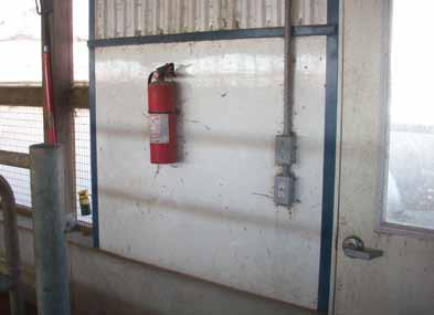 Photo of a fire extinguisher properly mounted on the wall of a barn, next an exit.