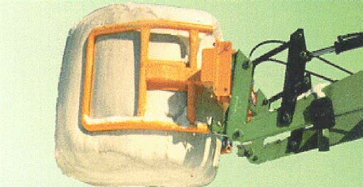 Individually wrapped round bale and handling loader attachment