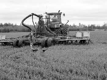 Picture of a direct-flow application unit on tractor pulling manure spreader over field.