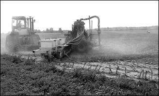 Photo shows a tractor pulling a drag hose for liquid manure application in a field.