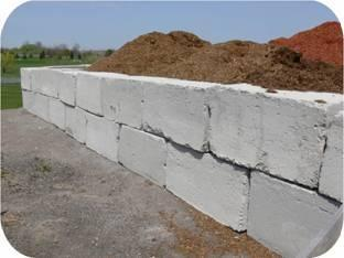 The 0.6 m x 1.2 m x 1.2 m (2 ft x 4 ft x 4 ft) concrete blocks used to build a storage for compost material at this landscaping firm are perfect for building a horse manure storage.