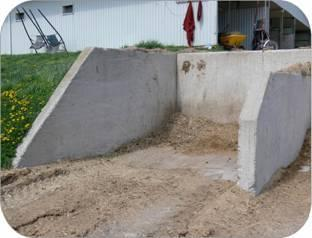 Storage in the side of a hill makes it easy to dump wheelbarrows. Install safety stops at the top edge.