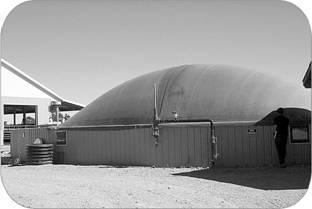 This image shows an on-farm anaerobic digester in Ontario. It is a manure storage with a large rubber dome on top.
