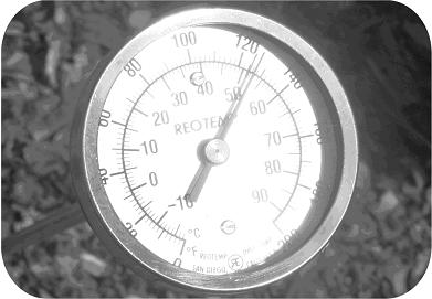 Long-stem thermometer inserted in compost pile recording a temperature of 51°C (124°F).