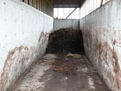 Interior view of a concrete bin showing wall height and some substrate at the furthest end of the bin.