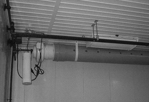 A photo showing a rigid duct (mounted at ceiling height) with a fan on the left end and air distribution holes, along the duct, to assist in air circulation.