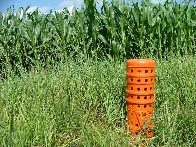 Photo showing an orange riser inlet in a field.