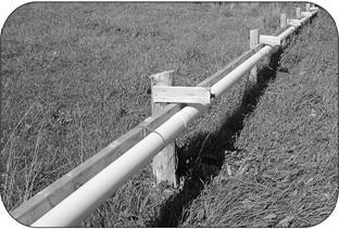 When the holding tank reaches a sufficient volume of runoff, the pump sends the liquid through a pipe that on this farm is 40 m (130 ft.) long with 1.9 cm (3/4 in.) holes drilled every 4.5 m (15 ft.) to allow for an even distribution across the entire vegetated strip.