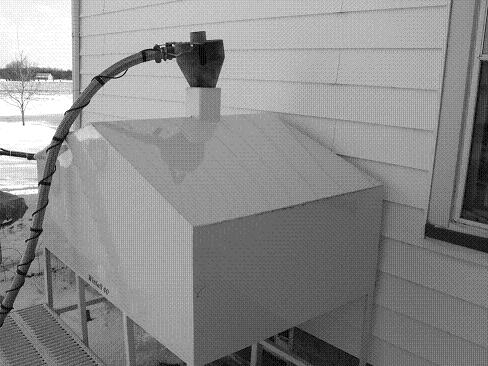 This large welded corn hopper stores about a month's fuel outside a farmhouse. Corn is carried by gravity inside a pipe that passes through a basement window. Inside, the corn flows directly into the stove hopper. The gray hose is used to pneumatically transfer shelled corn from a small wagon to the storage hopper.