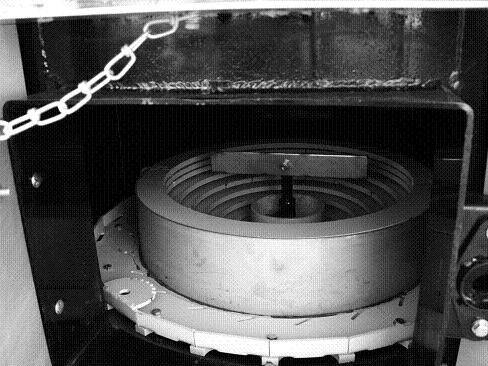 An empty combustion chamber of a large corn-fuelled hydronic furnace. The silver bar located in the centre of the combustion chamber rotates to break up and move the clinkers off the fuel mound.