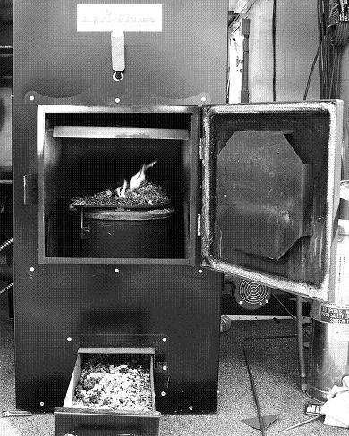 This corn burner uses a bottom fuel delivery system. Burnt corn can be seen mushrooming up and eventually falls into an ash tray.