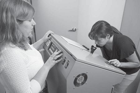 Figure 2 is a picture of a woman in a laboratory, placing her nose against a large grey machine in order to assess a smell sample. A female technician stands to the left of the equipment pressing the key pad on the machine.