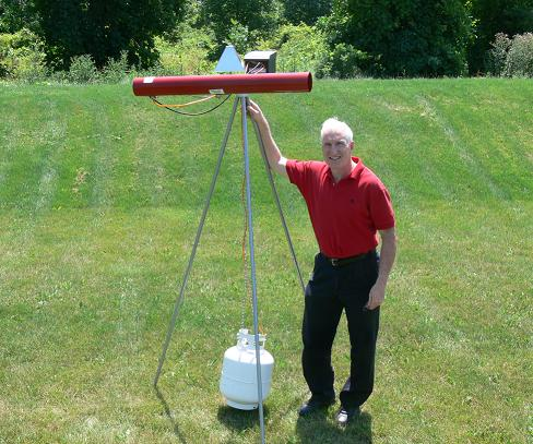 This picture shows the author standing beside a bird banger mounted on its tripod and with its propane tank hanging below. Its cylindrical red barrel is about 0.3 m above the author's head.