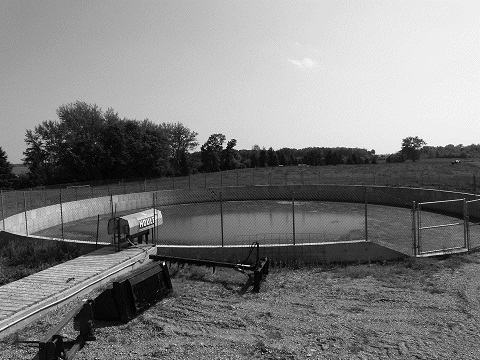 A photo of an in-ground, concrete, circular manure storage tank. The tank is surrounded by a wire fence and situated next to a corn field.