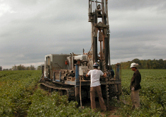Picture of two men operating a mobile drilling rig in a field.