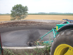 Picture of the back of a tractor backed up to a circular manure tank. The tractor is powering the agitator to stir the liquid manure in the tank.