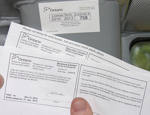 This photo shows a contractor holding his Business and Operator licences issued by OMAFRA under the Agricultural Tile Drainage Installation Act.