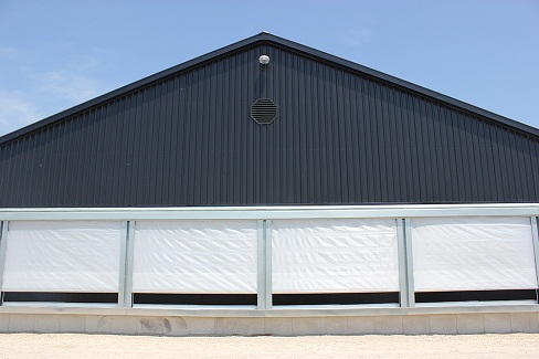 Picture of evaporative cooling pads with an exterior weather protection curtain (white curtain) that is partially closed.