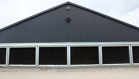 Picture of the tunnel inlet end of the barn with an evaporative cooling pad installed. Exterior covers have been pulled in to expose the black cooling pads.