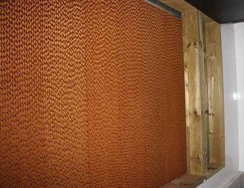 Picture of an evaporative cooling pad from inside the barn. The corrugated make-up of the reddish-brown pad material is visible.