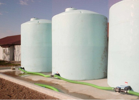 Photo of a farm site showing three large polyethylene storage tanks located on a concrete slab with small spill containment wall (1 ft. high) around the perimeter of slab.