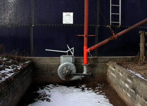 Picture of a side-mounted pump attached to an above-ground steel manure storage structure.