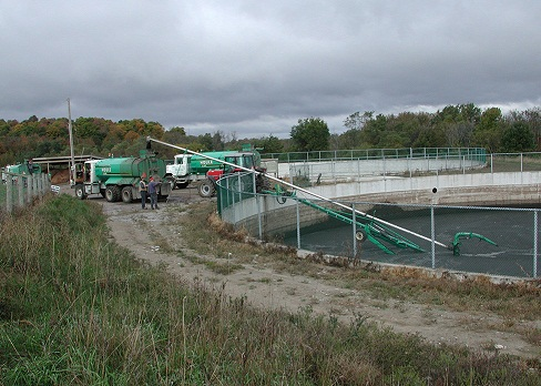 Picture of agitated manure in a circular, in-ground manure storage, being pumped into a tanker truck.