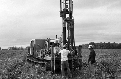 This image shows a mobile drilling rig in a soybean field. The rig is used to take soil core samples for permeability testing.