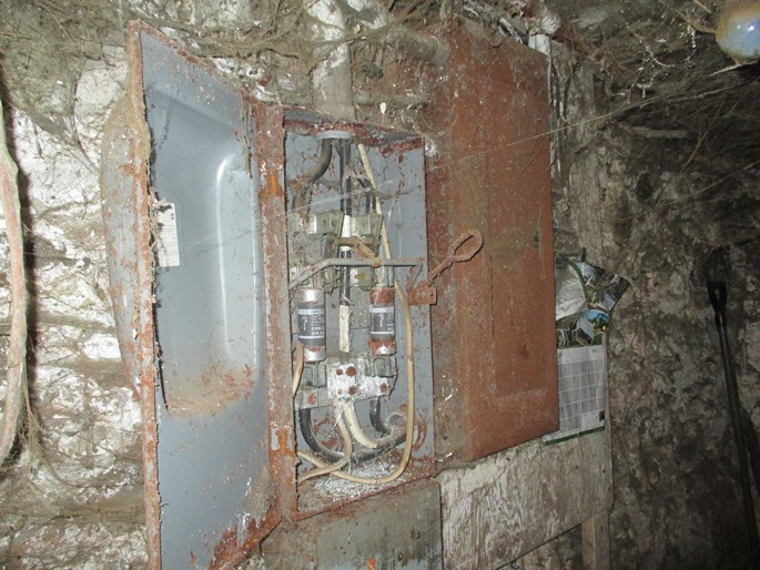 This is a photograph of an electrical disconnect panel installed in a barn.  The panel was operational at the time the photograph was taken.  There is a large amount of cobwebs attached to the wall around the panel.  The exterior of the panel is rusty.  The access door of the panel is open to show heavily corroded disconnect switch components and fuses.