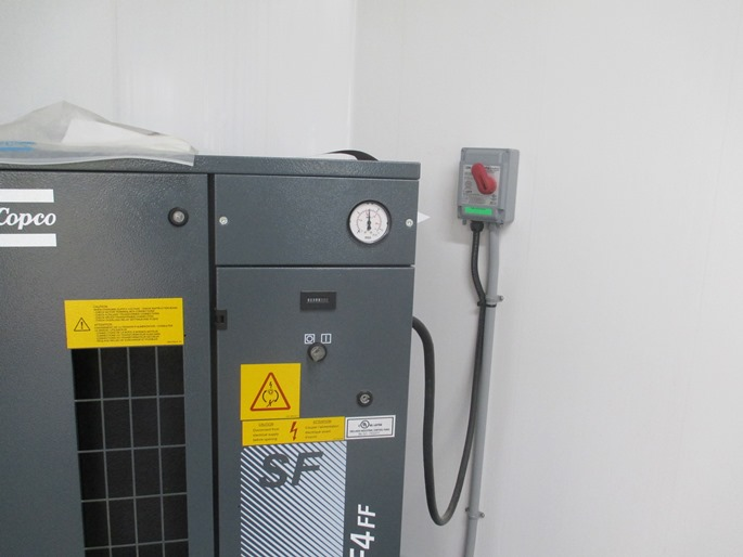 This is a photograph of the motor mounted off the ceiling in a dairy barn.  A hardwired cable is supplying electricity to a junction box close by to the motor.  A wet-rated plug and receptacle is used to supply electrical power from the junction box to the motor.  The wet-rated plug and receptacle incorporates a seal to avoid the egress of water or corrosive gases into the plug and receptacle components.
